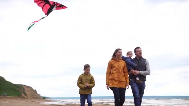 Rodina walkin na břehu oceánu. Muž, Žena, chlapec a děvčátko
