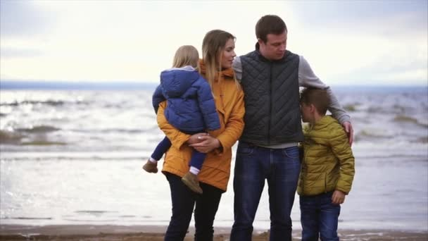 The husband and his wife stand with the children near the sea and enjoy the day