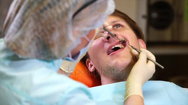 A female dentist examines the oral cavity of a patient with a dental mirror