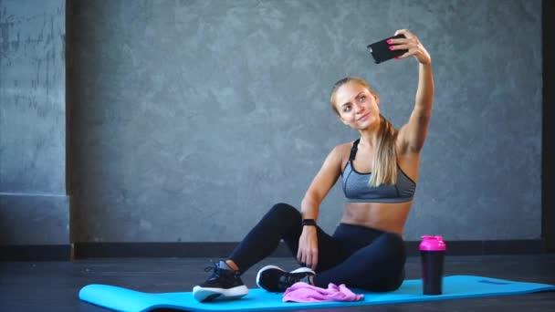Sportovní žena pořídí fotografie na telefonu po cvičení ve fitness klubu