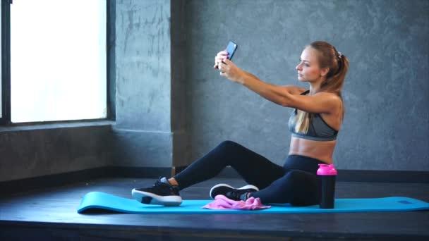 Mladá dívka s dobrou postavu díky selfie na mobilním telefonu v tělocvičně