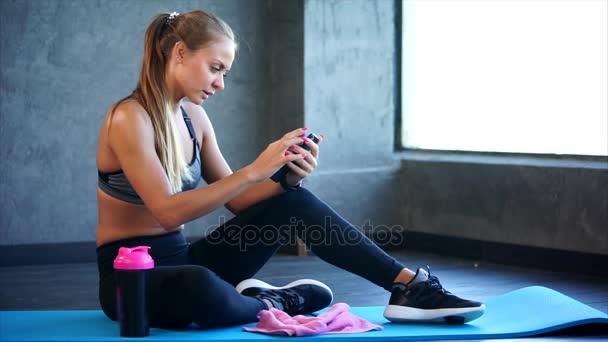 Žena v posilovně s smartphone. Ona sedí na podložce a pomocí smartphonu