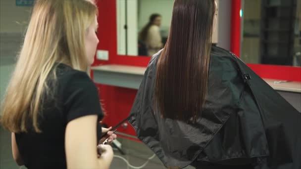 Žena holičství stříhání konečků vlasů, narovnávání a to česání