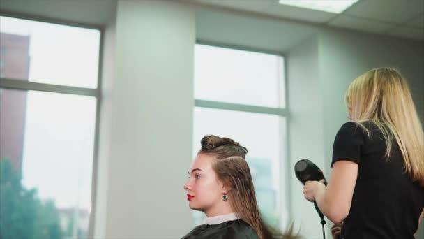 A szőke fodrász kiegyenesíti a nedves haját, egy hajszárító és a fésű