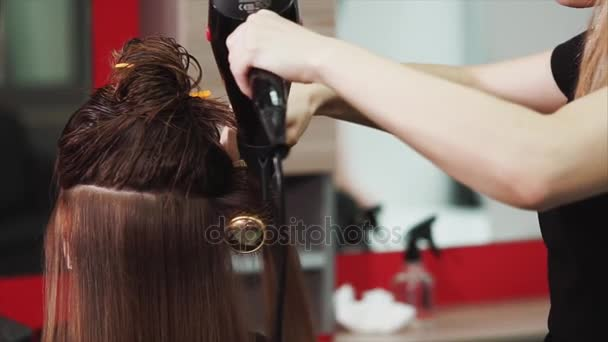 close up shot of the process of drying hair with a hair dryer and comb