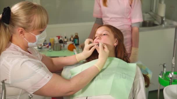 A fogorvos szárítás egy könnyű pecsét egy tizenéves lány, aki eljött, hogy kezelje a fogát