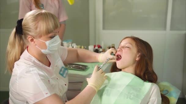 Zahnärztin injiziert Betäubungsmittel an ihre Patientin im Zahnschrank.