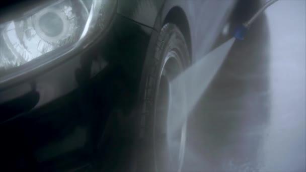 Muž mytí pneumatik na mytí aut, samoobslužné služby