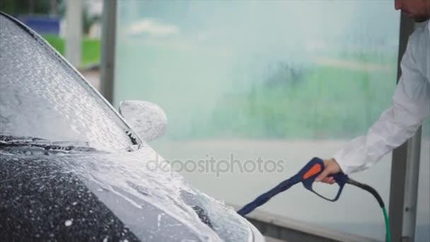 Muž Stříkání pěny na jeho auto. Samoobslužné mytí aut