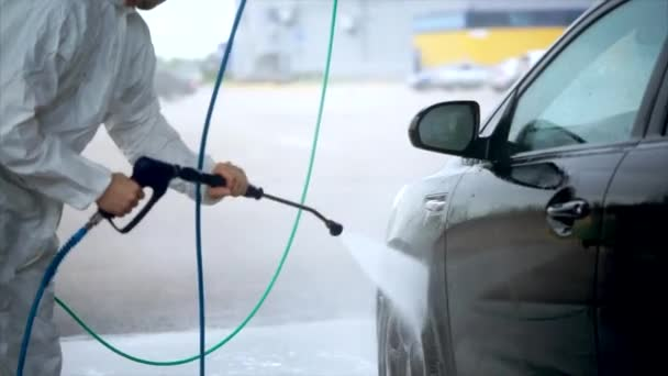 Young caucasian man washes his car carefully. Car washing self-service.