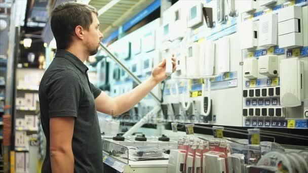 Muž v obchodě elektronika je volba intercom bezpečnostní systém a výstrahy