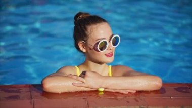 Redhead woman relaxing in the pool. She standing on the side of swimming pool