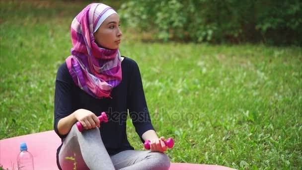 современный мусульманская женщина в парандже опираясь на коврик для йоги на улице