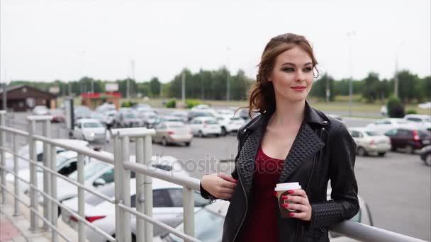Mosolygó nő egy pohár kávét tartja a kezében, és keresi a távolság