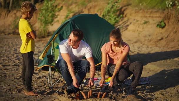 Rodina jíst pečené klobásy na prázdniny na venkově