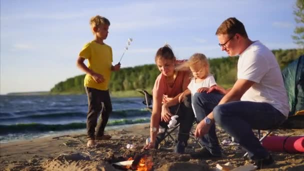 Kids and parents roasting marshmallow on campfire