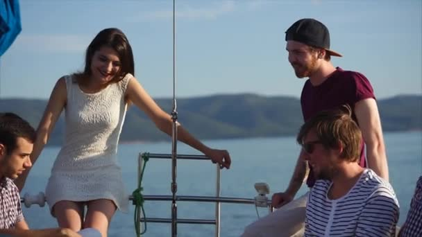 A company of young and modern friends is hanging out on a yacht in the summer