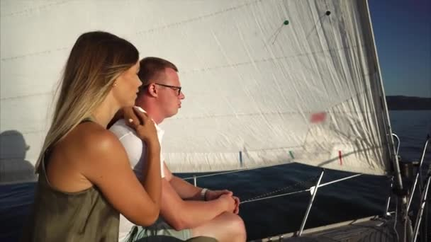 Cheerful guy and girl are resting on a sailboat in sunny summer day