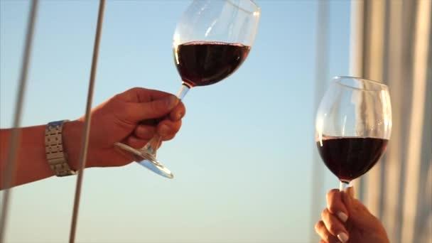 Cinkání sklenic s červeným vínem do rukou muže a ženy, detail
