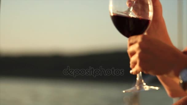 Couple drinking red wine on the yacht at sunset