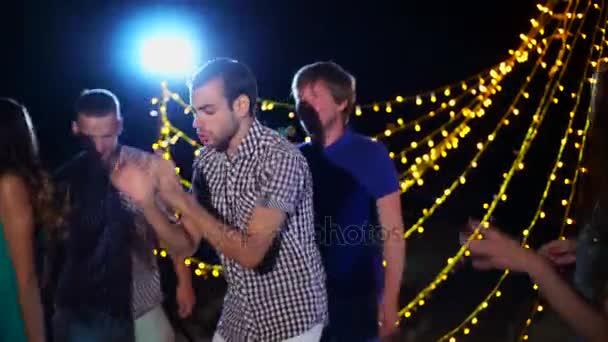 fröhliche Menschen tanzen bei nächtlicher Strandparty