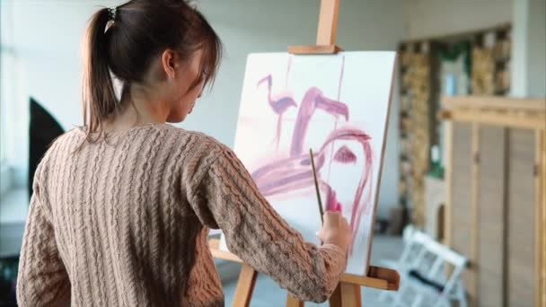 Woman paints swift strokes of pink flamingos in different angles, she uses brush