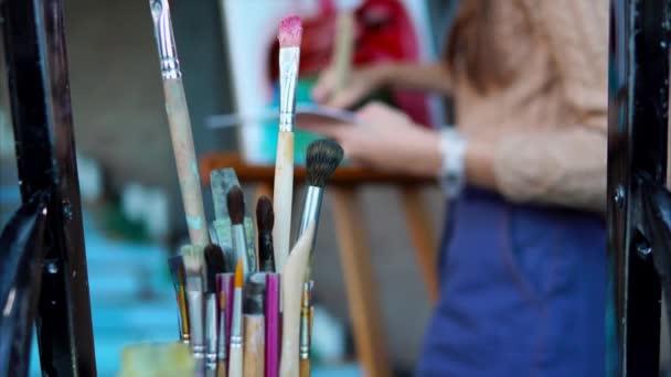 Nahaufnahme von schmutzigen Pinseln, im Hintergrund malt eine Frau ein Bild