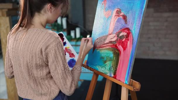 Artist during work, is painting picture with pink flamingos on blue background