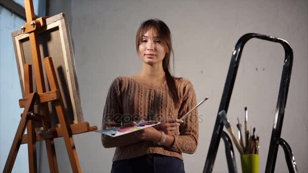Young girl is art school student, standing in workroom in evening time.