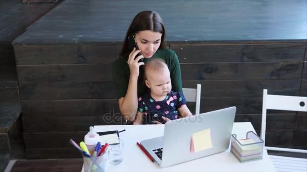 Az asszony beszél egy okostelefon, hogy jegyzetek és holding a gyermek az irodában