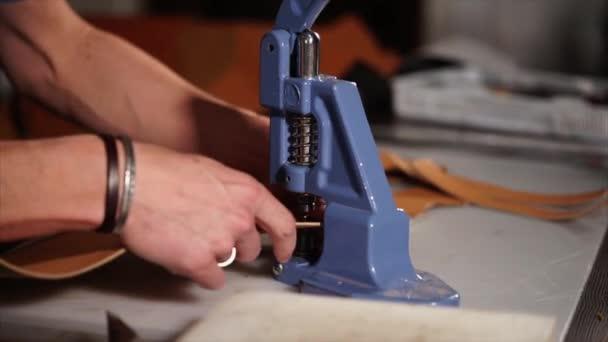 Řemeslník používá ruční lis pro instalaci kování na koženou dobré