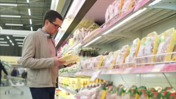 Muž zvolí kuře, si bere produkt z čítače v supermarketu