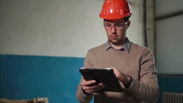 Muž inženýr s digitálním tabletu na staveništi