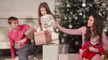 happy friendly family is folding gifts under big christmas tree