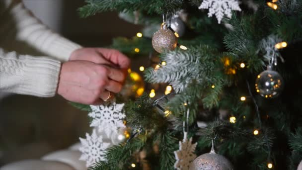 Mans hands are putting fake white snow-flakes on a Christmas tree in dark room