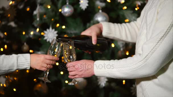 Mann und Frau gießen Champagner in Gläser, stehen am Weihnachtsbaum