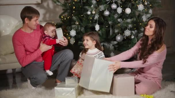 Young woman is giving christmas gifts to her husband, daughter and ...