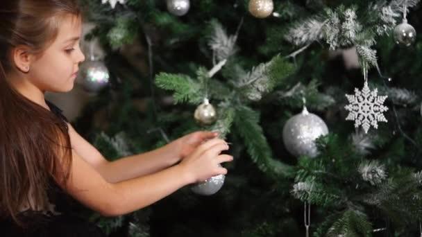 Malá školačka je oblékání vánoční strom v domácí, tradiční svátek