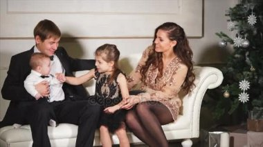 parents and their little children are sitting on the sofa near the decorated Christmas tree