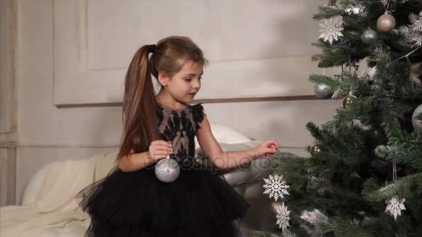 little girl dresses a Christmas tree before the holiday, the child hangs on branches bright balls