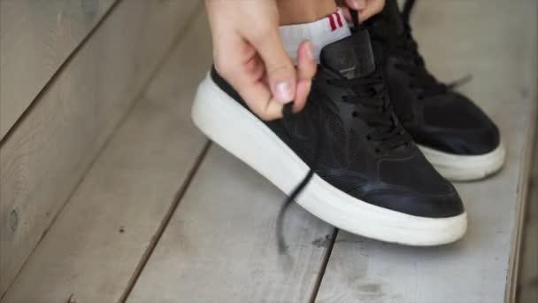 Frauenfüße stecken in schwarzen Sportschuhen, Hände binden Schnürsenkel, Nahaufnahme