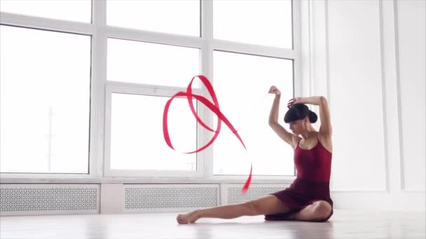 Graceful gymnast is twisting red tape, sitting in a dance hall