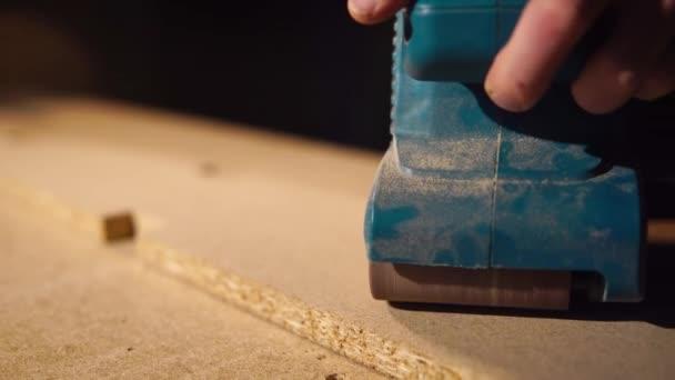 Detailní záběr záběr ruky tesaři, kteří leštidla dřevěný povrch s vrtačkou