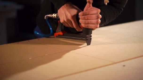 Detailní záběr záběr mans ruce, kdo používá sešívačka tesařské práce při tvorbě nábytku