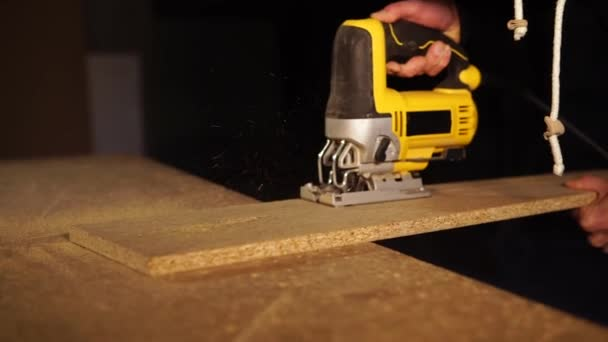 Carpenter works with electric saw