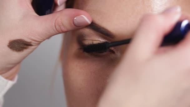 Zavřete a pak vystřelí make-up umělci rukou, který dá řasenka na oči klientů