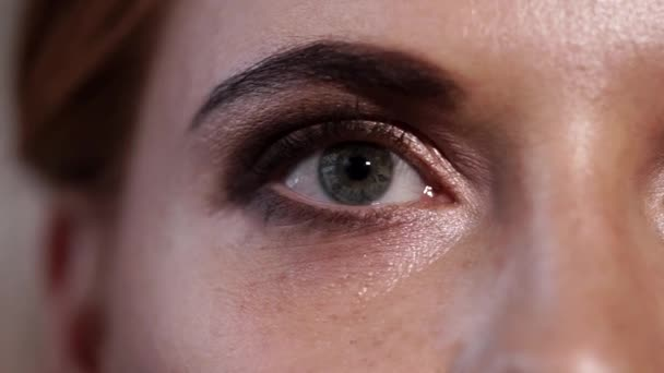 Detailní záběr záběr šedomodré oku dospělé ženy, která bliká a zavře oko jí