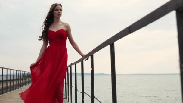 A divat modell öltözött hosszú selyem ruha pózol a mólón nappali