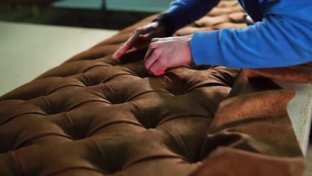 Worker is covering a carcass of sofa by fabric, stretching and tightening