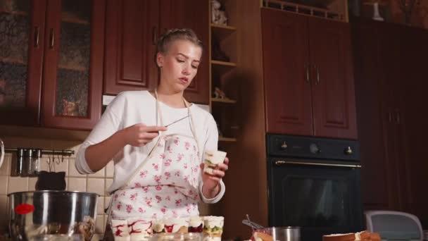 Mladá krásná dívka je vyhlazování topy zmrzliny v brýlích v kuchyni